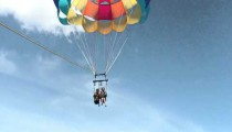 Two girls descending to the water in a parasail.