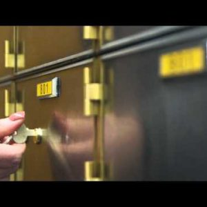 Close-up of hand and key opening a safety deposit box.