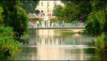 People on a bridge spanning a pond with a fountain.