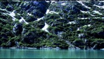 Traveling time-lapse of the snowy and rocky shore of Glacier Bay, Alaska.