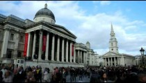 Time-lapse of Trafalgar Square buildings and crowd in London.