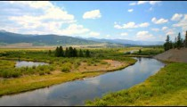 Time-lapse of plains and river with clouds above.