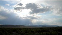 Time-lapse of the sun coming through clouds over a landscape.