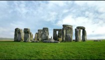 Wide time-lapse of Stonehenge with white clouds.