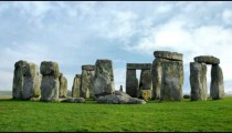 Stonehenge time-lapse with white clouds in the background.