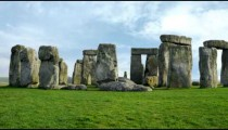 Panning time-lapse of Stonehenge with white clouds.