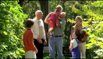 Parents and grandpa greet three children.