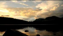 Silhouetted time-lapse of a mountain lake at sunset.