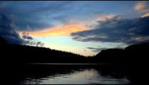 Time-lapse of a mountain lake and clouds at sunset.
