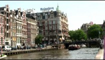 Buildings alongside a canal with passing ferries in Amsterdam.