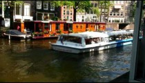 Ferry passing a houseboat on a canal in Amsterdam.
