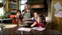 Three children helping their mother prepare food.