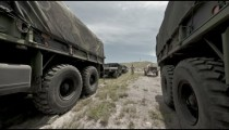 Time-lapse filmed between covered convoy trucks at a military training.