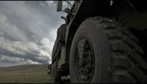 Dollying time-lapse alongside a military covered truck.
