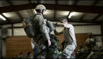 Soldiers loaded with gear waiting at parachute training.