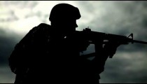 Silhouette of soldier using weapons at firing range