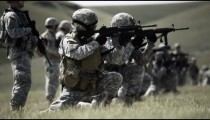 Soldiers kneel to fire rifles