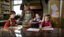 Children helping their mother in the kitchen.