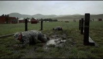 Muddied soldiers crawl in an obstacle course