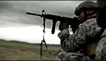 Kneeling soldier shoots M4 rifle in target practice