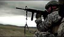 Kneeling soldier shoots M4 rifle in target practice