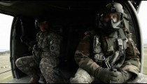 Two soldiers inside flying helicopter