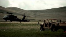 Helicopter landing in field with surrounding Humvee and soldiers