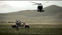 Shot from ground of Black Hawk helicopter approaching Humvee.