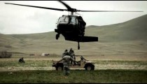 Black Hawk helicopter hovering above Humvee while soldier gives signals to pilot.