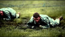 Soldiers crawling under low barbed wire at an obstacle course.