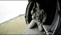 Wide angle shot from in Black Hawk helicopter flying and soldiers in the helicopter.