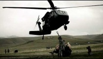 Black Hawk helicopter and soldiers rigging fuel tank on trailer to be lifted.