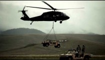Shot of Humvee being set down by Black Hawk helicopter in field.