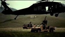 Static shot of soldiers attaching Humvee to Black Hawk helicopter.