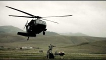 Shot from field of Black Hawk helicopter and soldiers preparing to haul off cargo.