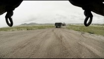 Shot from under vehicle in convoy training; on paved area.
