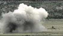 Slow motion clip of long range shot of large explosion.
