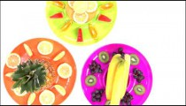 Rotating shot of an assortment of fruit on plates.