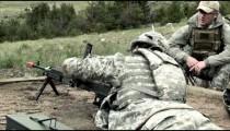 Clip of soldier loading chain machine gun at training range.