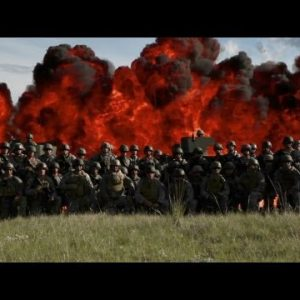 Panning shot of a group of soldiers lined up with explosion behind.