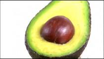 Close shot of a cut avocado rotating on a white screen.