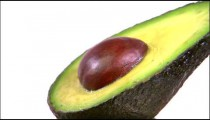 Close shot of half an avocado rotating on a white screen.