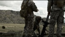 Instructor with soldiers on mortar range aiming mortar launcher.