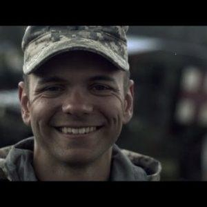 Slow motion clip of soldier smiling while snow falls.