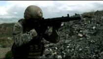 Slow motion clip of soldier shooting automatic weapon.
