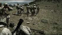 Slow motion clip of soldiers firing a mortar with instuctors.