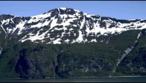 Traveling view of a snow capped mountain with water at the base, Alaska.