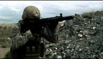 Slow motion clip of soldier shooting suppressed automatic weapon.