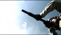 Slow motion clip, from below, of soldier shooting automatic weapon.