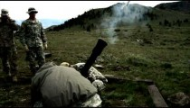 Slow motion shot of soldiers firing a mortar at range.